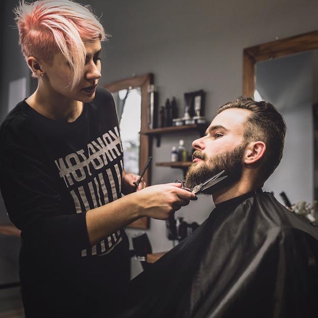 Woman grooming beard of stylish client Free Photo