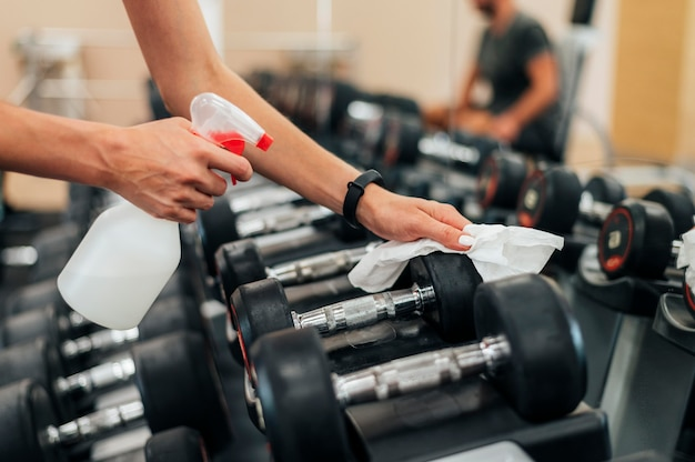 Woman at the gym disinfecting weights before using them Free Photo