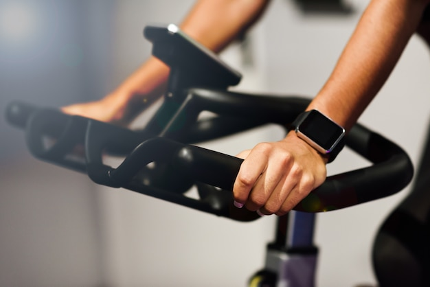Woman at a gym doing spinning or cyclo indoor with smart watch Free Photo
