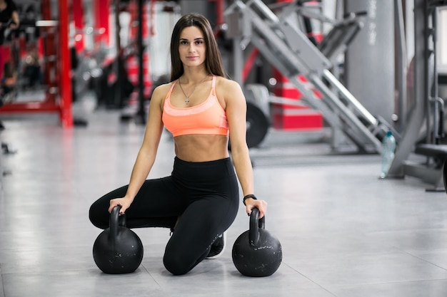 Woman at gym with kettlebells Free Photo