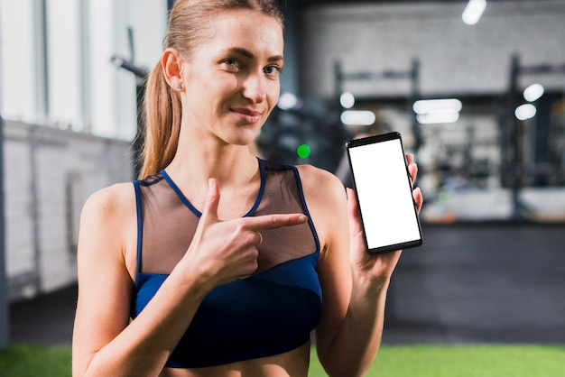 Woman in gym with smartphone template Free Photo