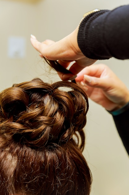 Woman hairdresser making hairstyle using curling iron for long hair of young female Premium Photo