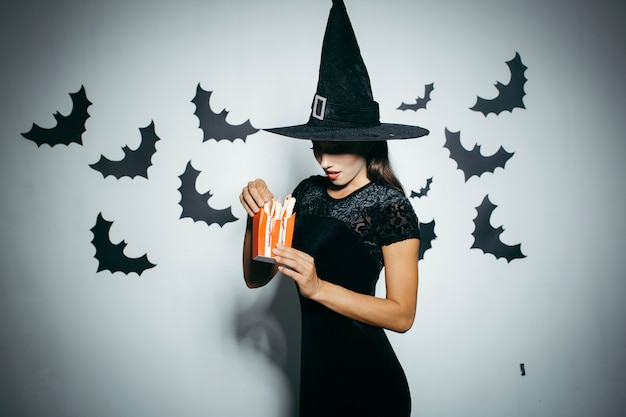 Woman in halloween hat with food box Free Photo