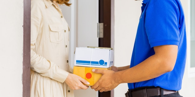 Woman hand accepting a delivery of boxes from deliveryman in blue uniforms at the doorway. Premium Photo