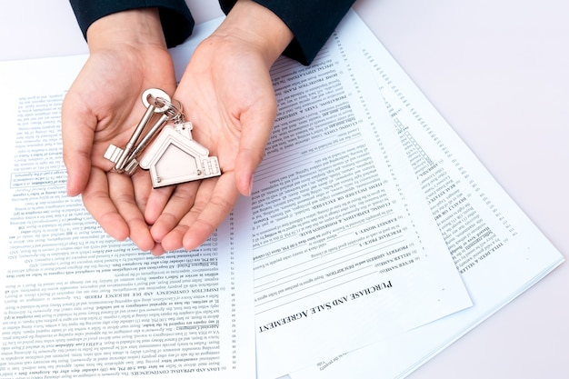 Woman Hand And Home Key Signed Contract And Keys Of The Property