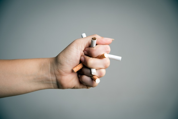 Woman hand breaking cigarettes. world no tobacco day Premium Photo