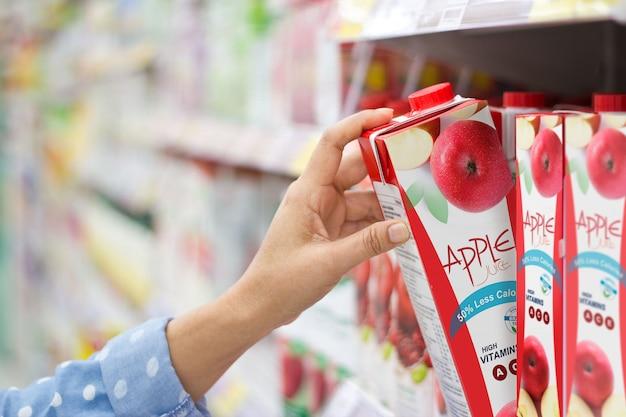 Woman hand choosing to buy apple juice on shelves in supermarket Premium Photo