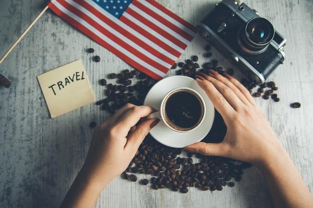 テーブルの上の旅行の概念と女性の手コーヒー Premium写真