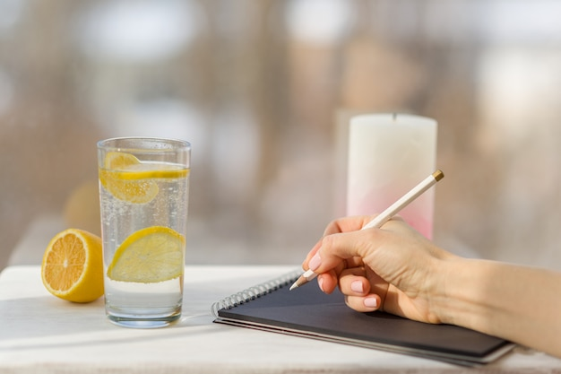 Woman hand draws in designer black notebook Premium Photo