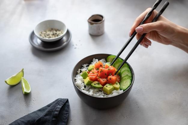 サーモン、米、アボカド、キュウリと箸ハワイポークボウルを食べる女の手。ダイエット食品。 Premium写真