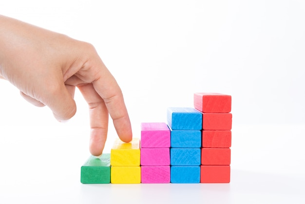 Woman hand finger walk on stacked wooden block like stairs. business concept. Premium Photo