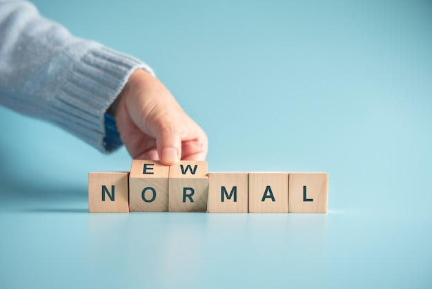 Woman hand flipping wooden cubes with new normal word. Premium Photo