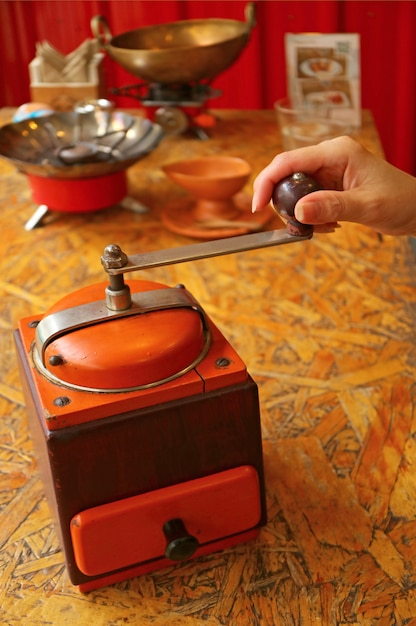 Woman hand grinding coffee beans in a vibrant color retro portable coffee grinder for homemade coffee Premium Photo