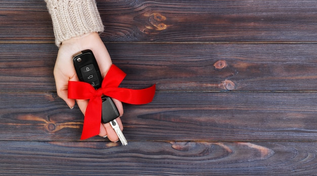 Woman hand hold car key with red bow. giving a car as a gift banner Premium Photo