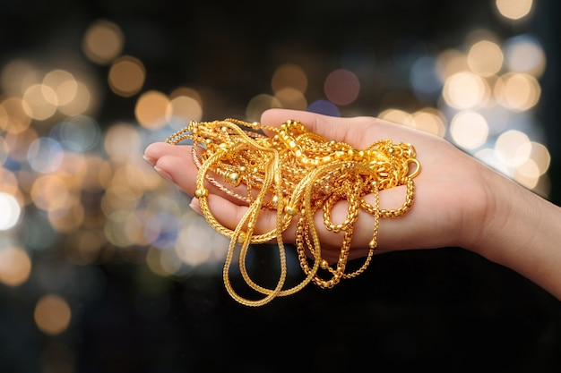 Woman hand hold gold bracelet and necklace jewelry Premium Photo
