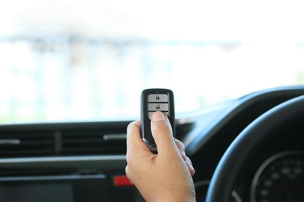 Woman hand hold a remote key car Premium Photo