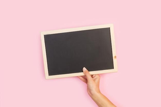 ピンクの背景に空白の黒板を持っている女性の手 Premium写真