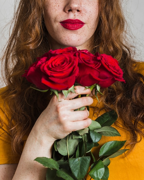 Woman hand holding bouquet of roses Free Photo
