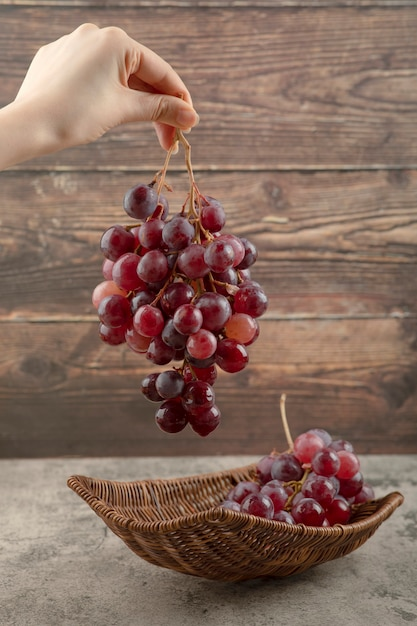 Женщина рука гроздь красного винограда на деревянных фоне. Бесплатные Фотографии
