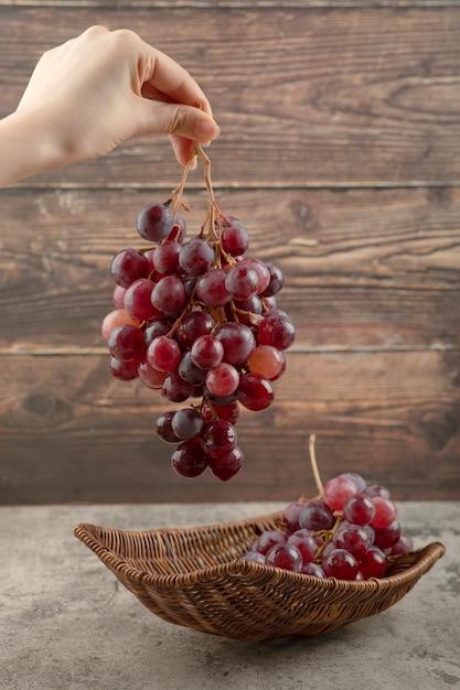 Mano della donna che tiene il grappolo di uva rossa su sfondo di legno. Foto Gratuite