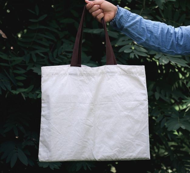 Woman of hand holding cotton tote bag on green leaf background. concept eco and recycling Premium Photo