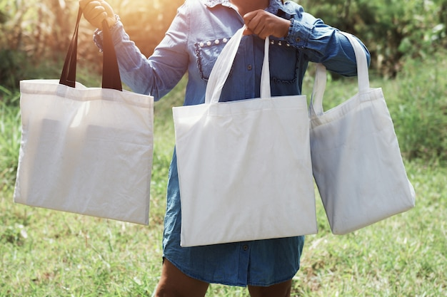 Woman of hand holding cotton tote bag three on green grass background. concept eco and recycling Premium Photo