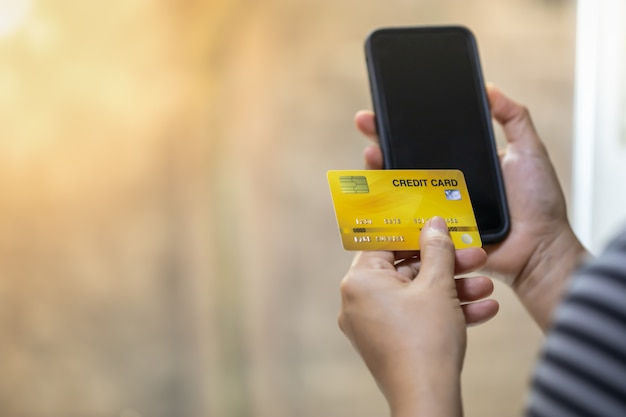 Woman hand holding credit card and smart mobile phone wiht copy space. Premium Photo