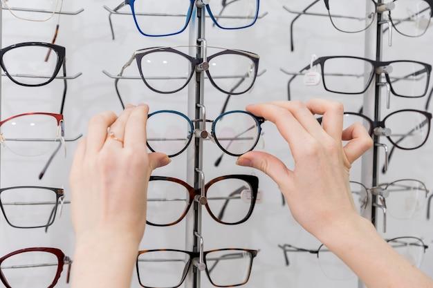 Woman hand holding eyeglasses in optics shop Free Photo