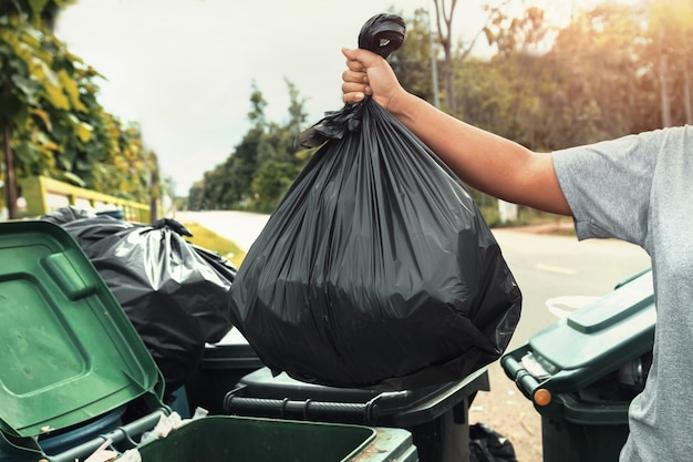 Woman hand holding garbage in black bag for cleaning in to trash Premium Photo