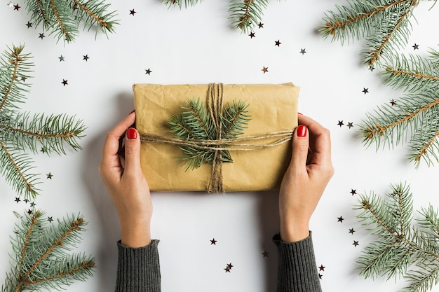 Woman hand holding gift box christmas decoration composition spruce fir brunch Free Photo