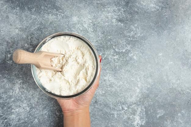 大理石に小麦粉のガラスのボウルを持っている女性の手。 無料写真
