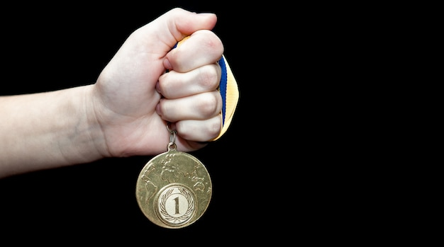 Woman hand holding gold medal against black background. award and victory concept Premium Photo