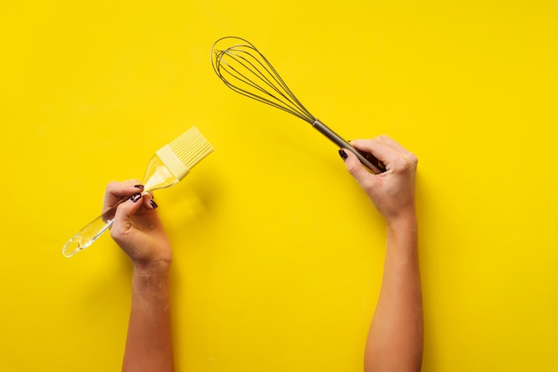 Premium Photo Woman Hand Holding Kitchen Utensils On Yellow Background Baking Tools Brush Whisk Spatula Bakery Cooking Healthy Homemade Food Concept Copy Space