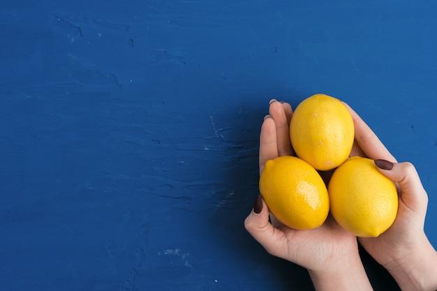 Woman hand holding lemon against classic blue background, top view Premium Photo