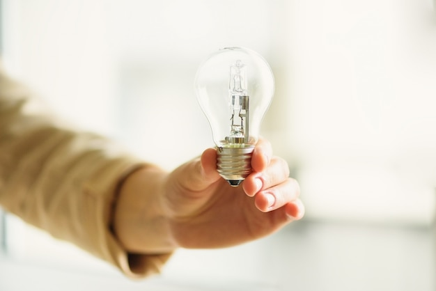 Woman hand holding light bulb on cream background with copy space. creative idea, new business plan, motivation, innovation, inspiration concept. Premium Photo