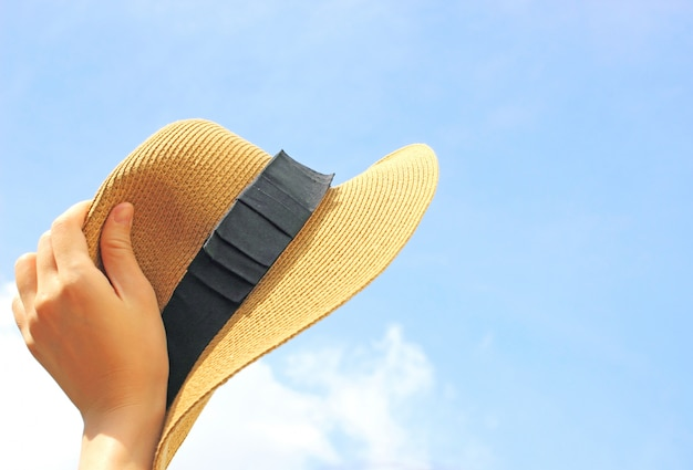 Woman hand holding panama hat with blue sky Free Photo