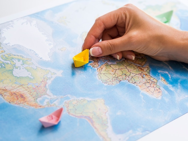 Woman hand holding a paper boat on a map Free Photo