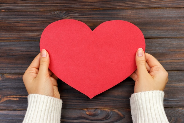 Woman hand holding paper red heart shape. copy space Premium Photo