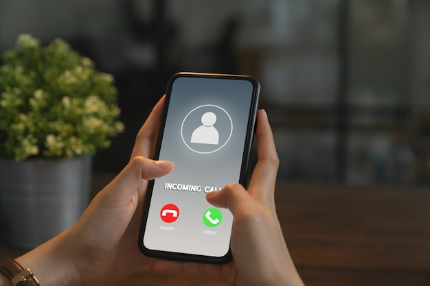 Woman hand holding phone and show screen incoming call. Premium Photo