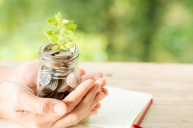 Woman hand holding plant growing from coins bottle Free Photo