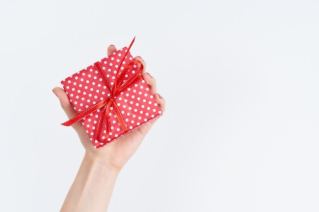 Woman hand holding red gift with ribbon, manicured hand with nail polish on white Premium Photo