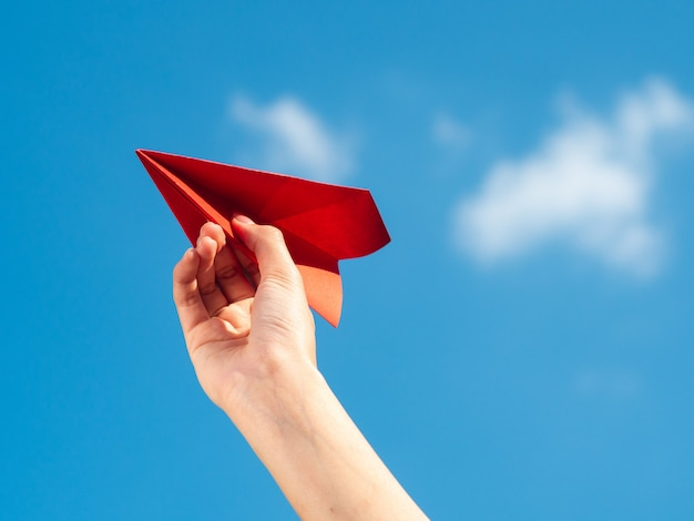 Woman hand holding red paper rocket with blue sky background. freedom concept Premium Photo