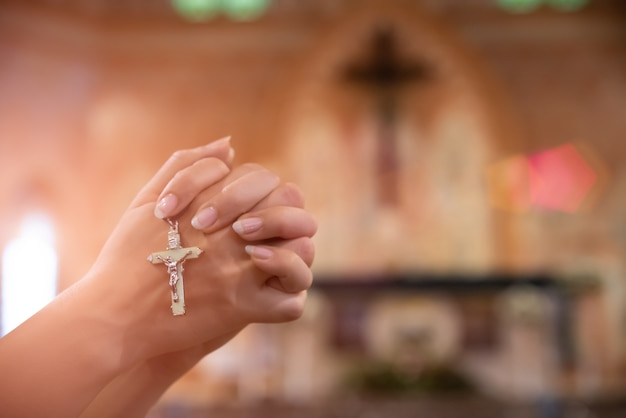 Woman hand holding rosary against cross and praying to god at church Premium Photo