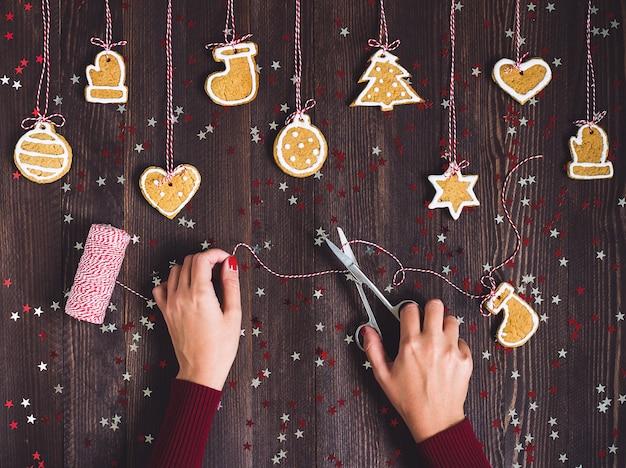 はさみを持つ女性の手はクリスマスツリーに掛かるためのジンジャーブレッドを準備します 無料写真