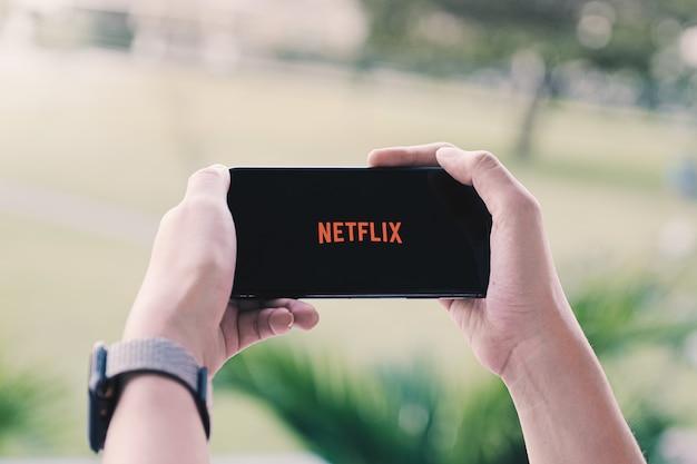 Woman hand holding smart phone with netflix logo Premium Photo