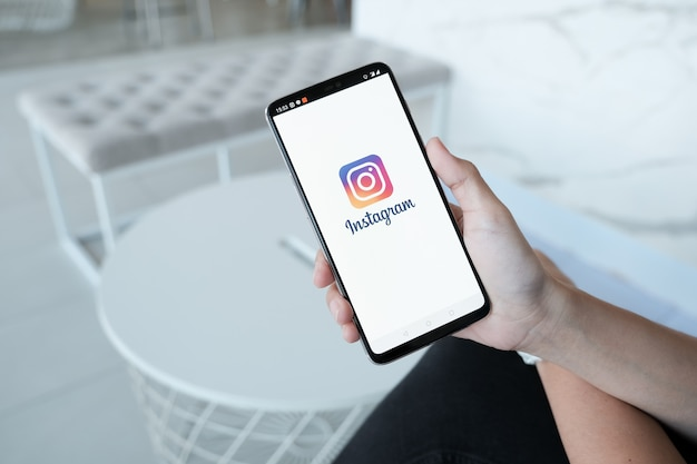 Woman hand holding smartphone with login screen of instagram application. instagram is largest and most popular photograph social networking Premium Photo