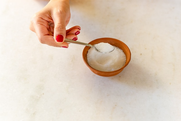 Woman hand holding spoon full of sugar health care concept. Premium Photo