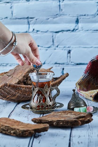 Mano della donna che tiene un cucchiaio di tè e vari dolci sulla tavola di legno blu Foto Gratuite