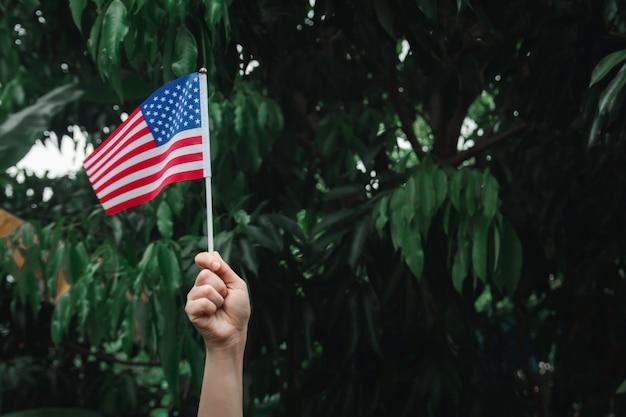 緑の森にアメリカ国旗を持つ女性の手 Premium写真