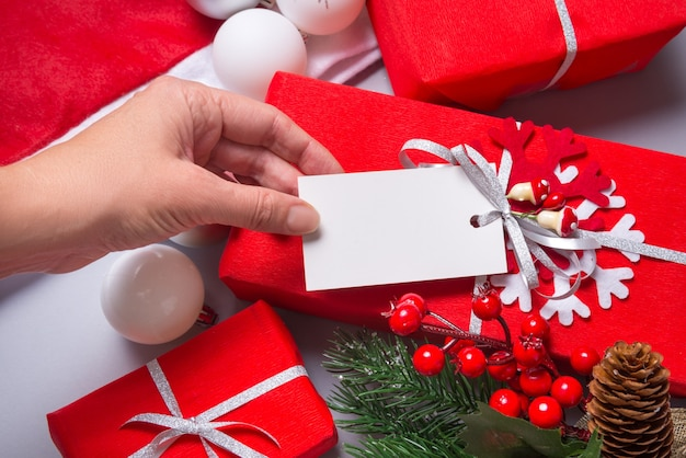 Woman hand holding white carton tag, label  on gift wrapped box Premium Photo